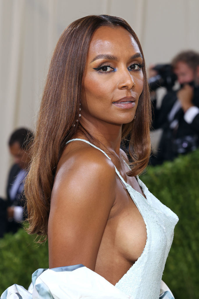 A close up ofJanet Mock as she poses by looking over her shoulder