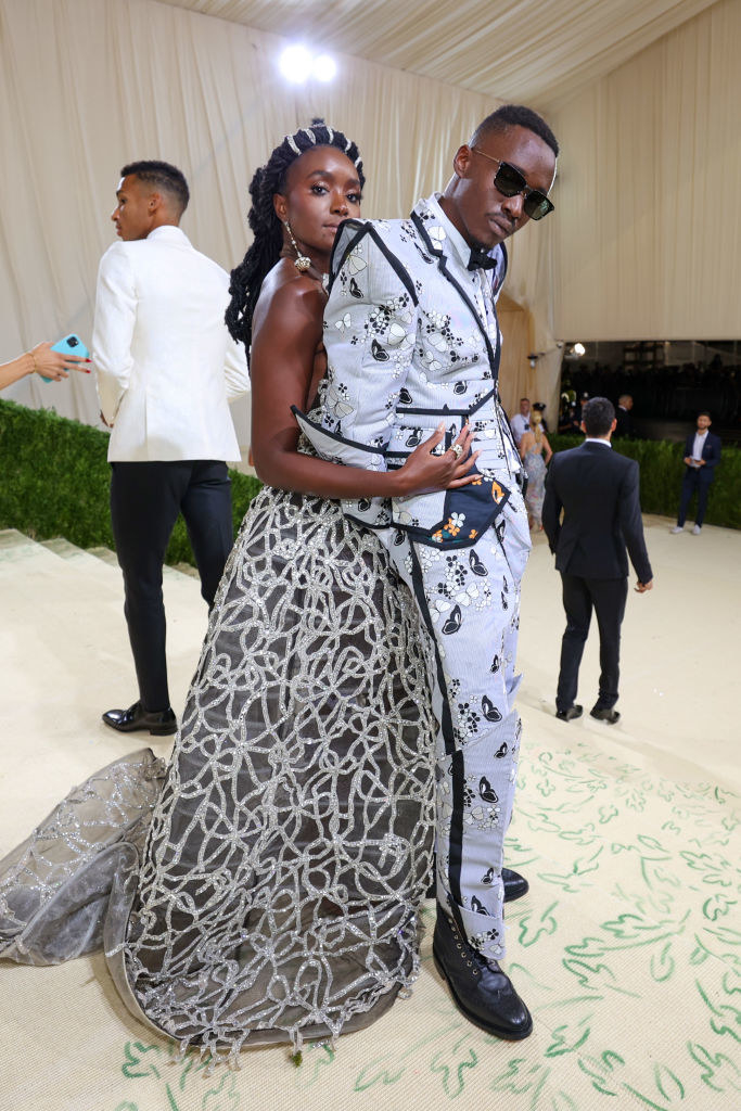 KiKi Layne wears a dark sparkly strapless gown and Ashton Sanders wears a light colored suit with dark butterflies on it