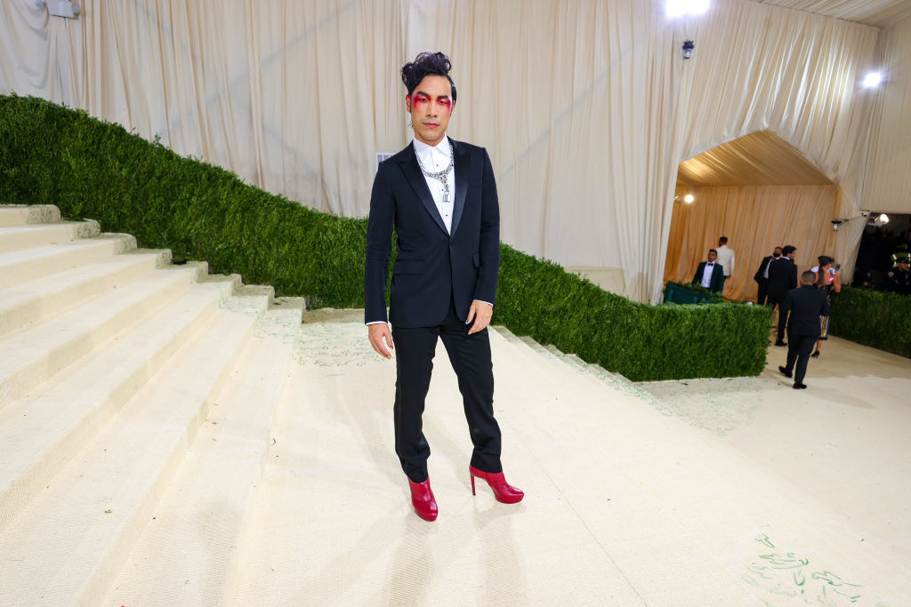 Eugene Lee Yang wears a dark suit and brightly colored heels