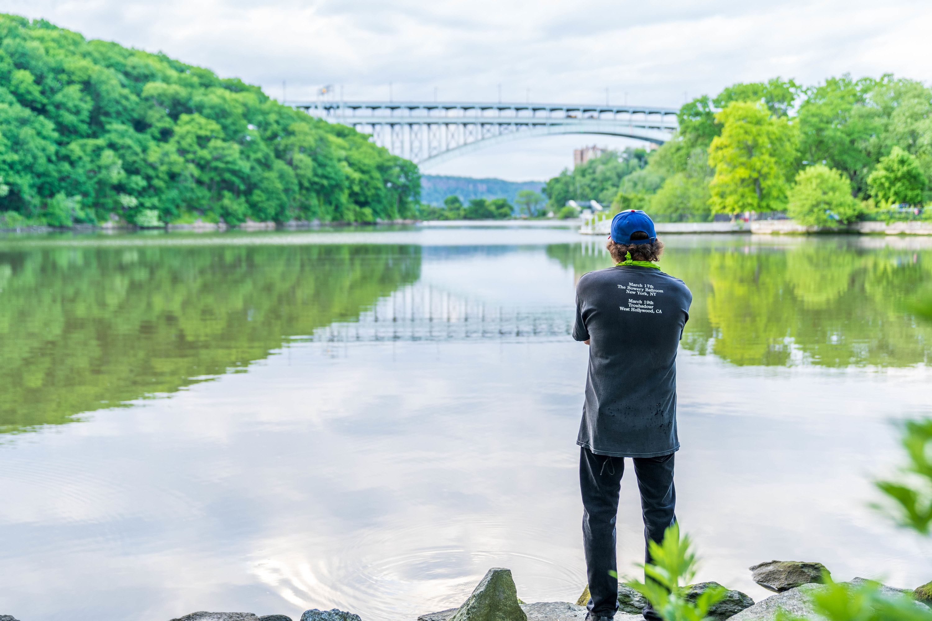 A man looking onto the Hudson River at Inwood Park.