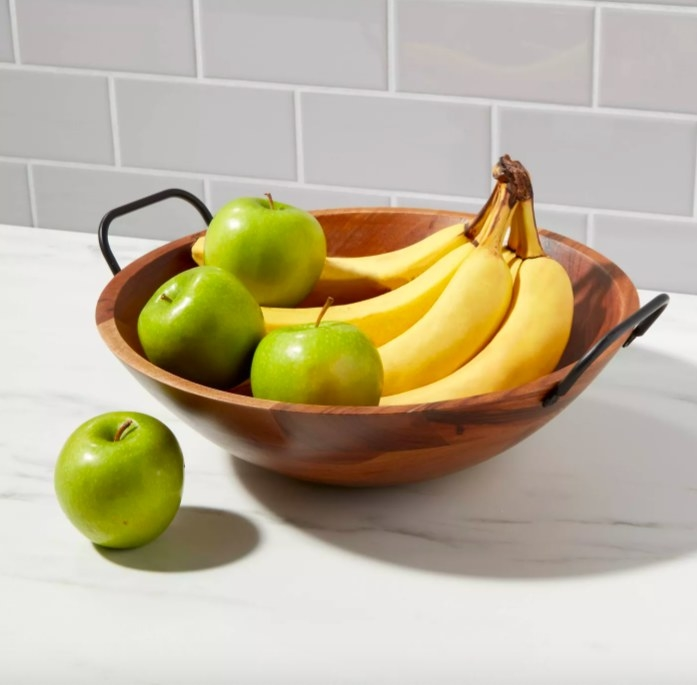 Wood bowl with black handles shown holding apples and bananas.