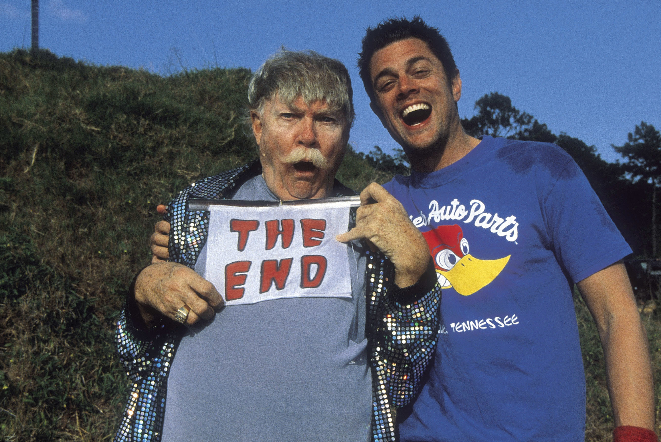"""Johnny Knoxville standing with Rip Taylor, who's holding a sign that says """"The End"""""""
