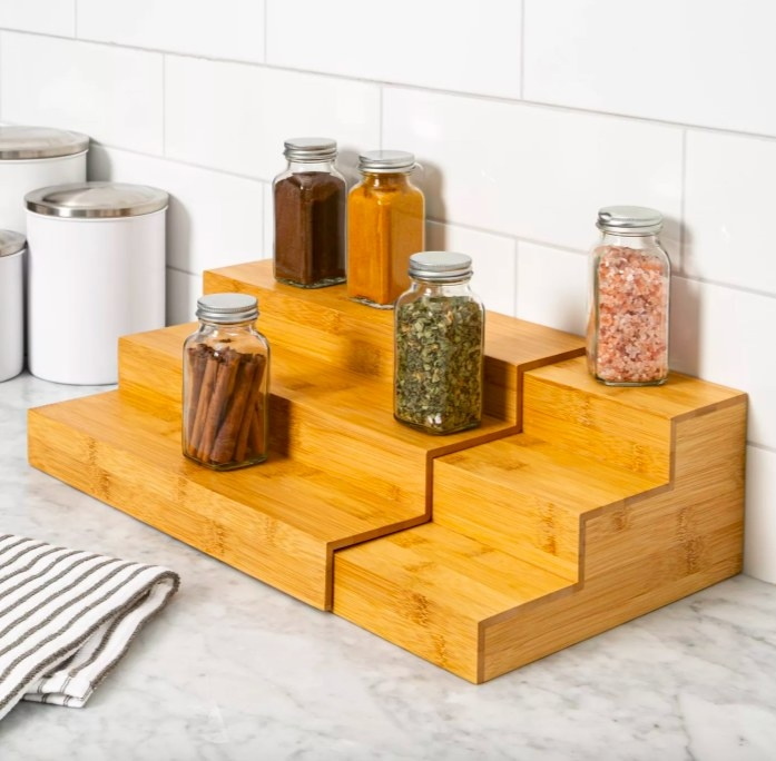 Bamboo spice rack shown sitting on a kitchen countertop with a couple of spice jars on it, canisters to the left of it and a kitchen towel in front of it.