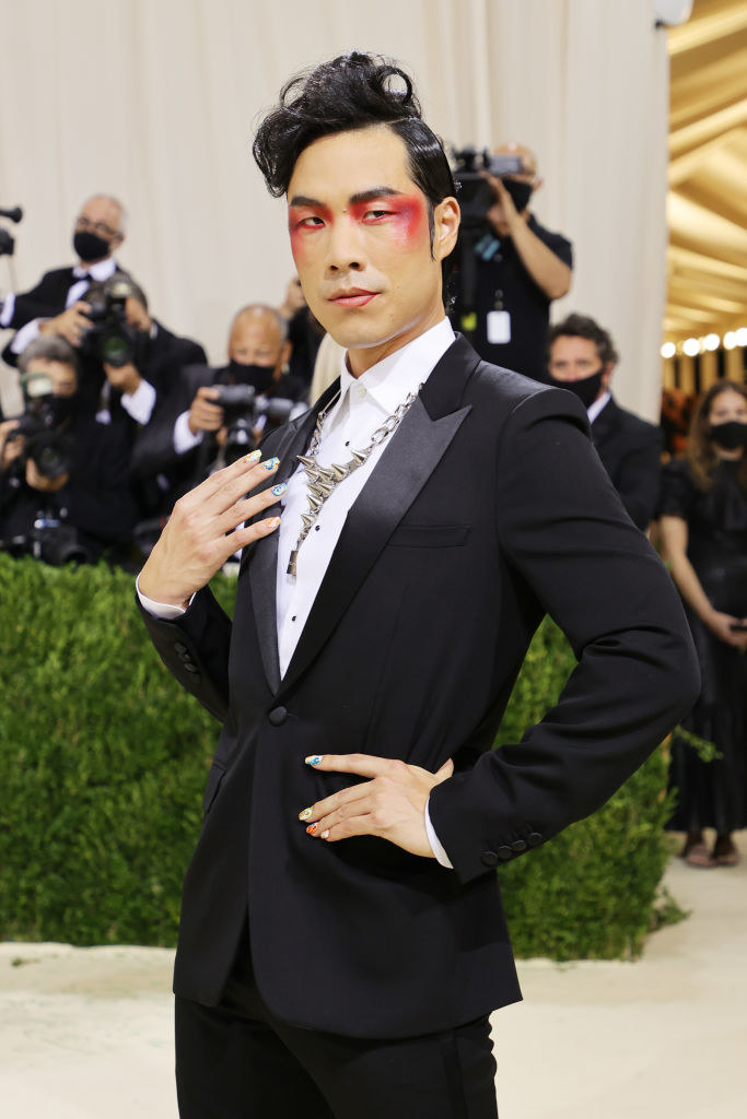 Eugene Lee Yang poses with his hand on his hip on the Met Gala red carpet