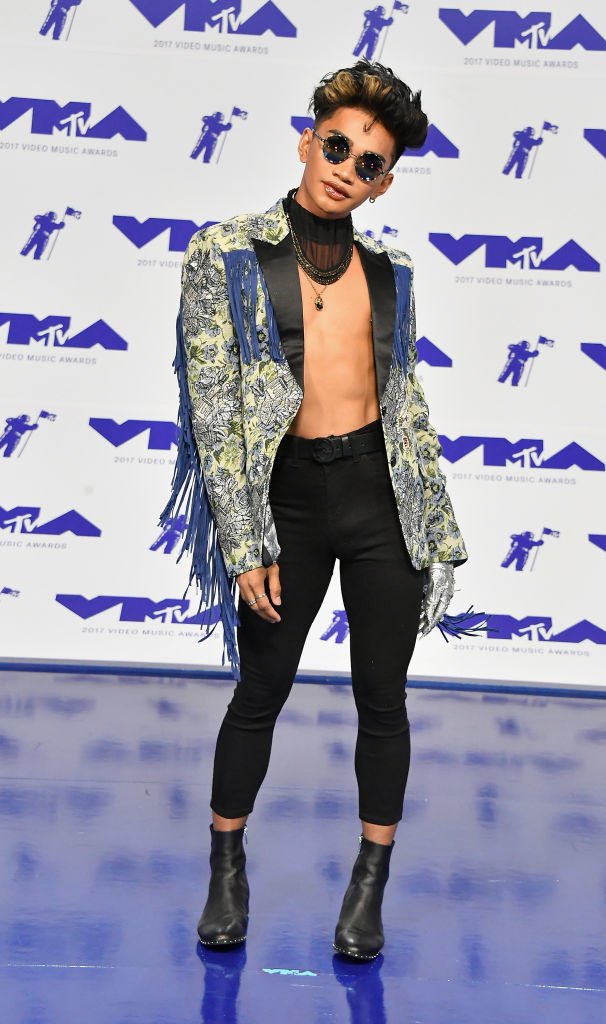 open paisley jacket with fringe on sleeve, no shirt, tight pants