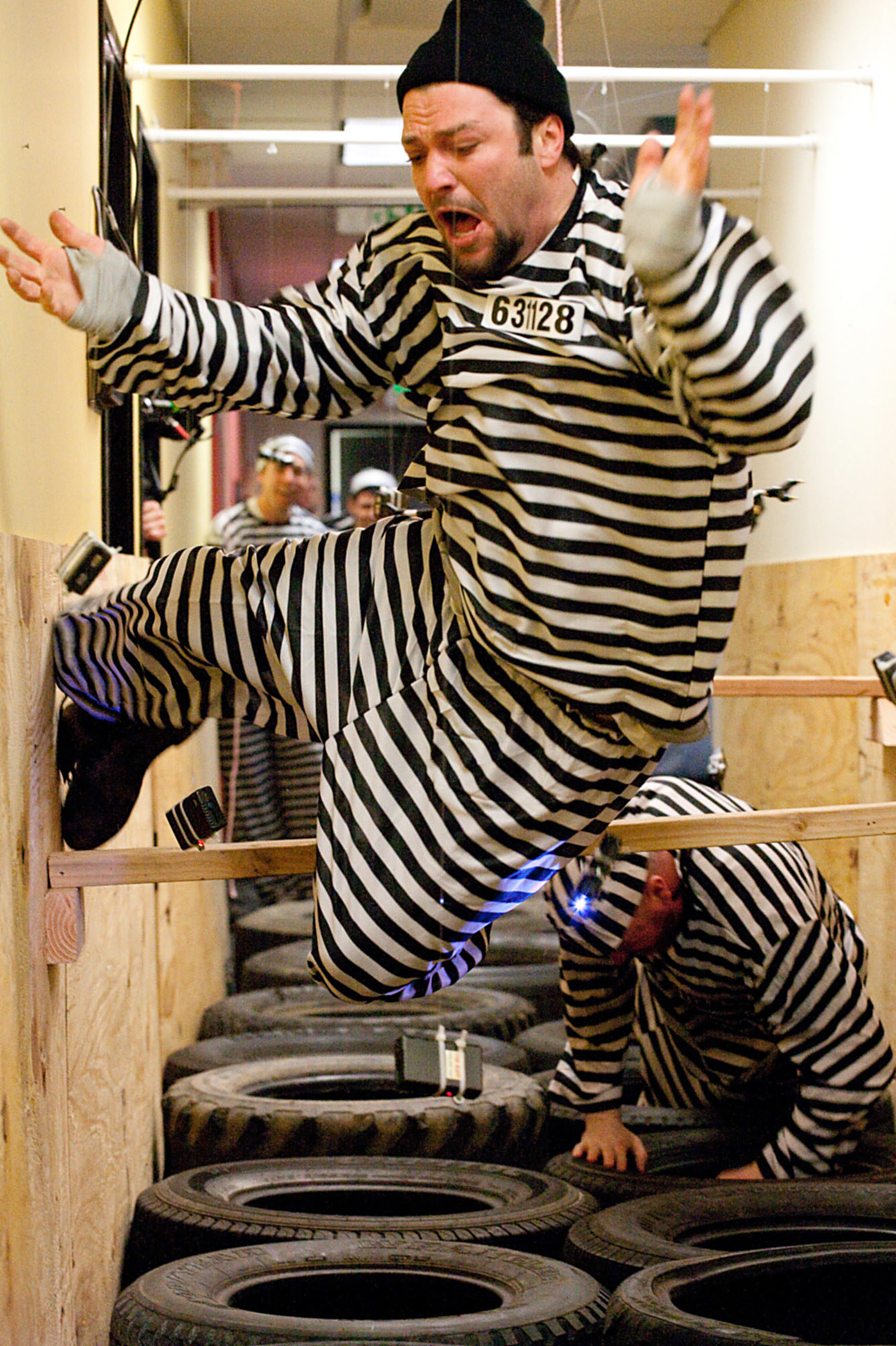 Bam dressed in a striped prison outfit and running through a hallway filled with Tasers