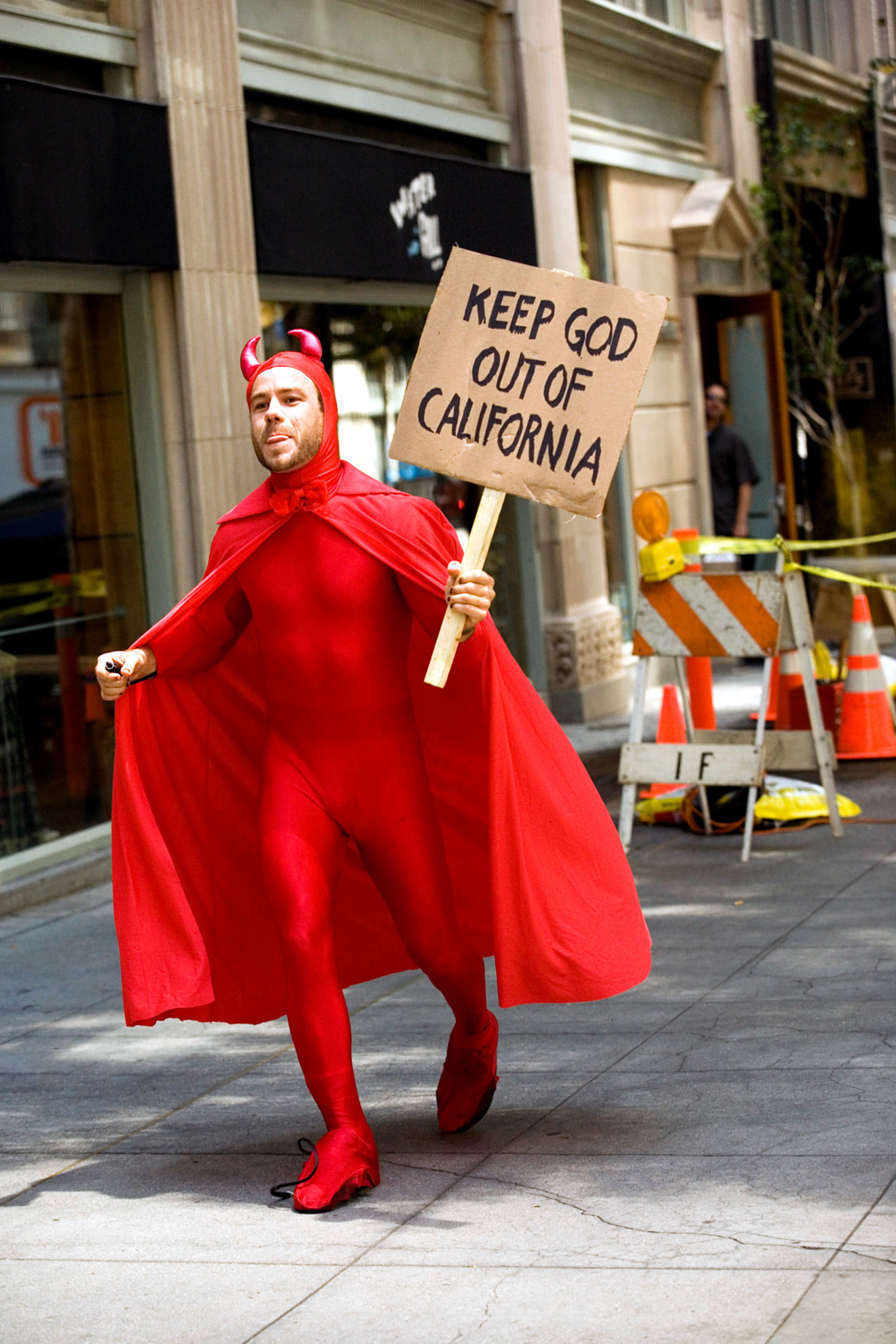 """Chris, dressed as a devil and holding a protest sign that reads """"Keep God Out of California"""""""