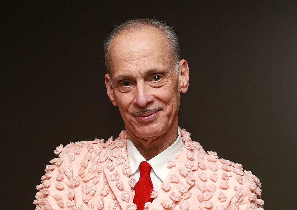 John Waters wearing a pink tufted suit at an event