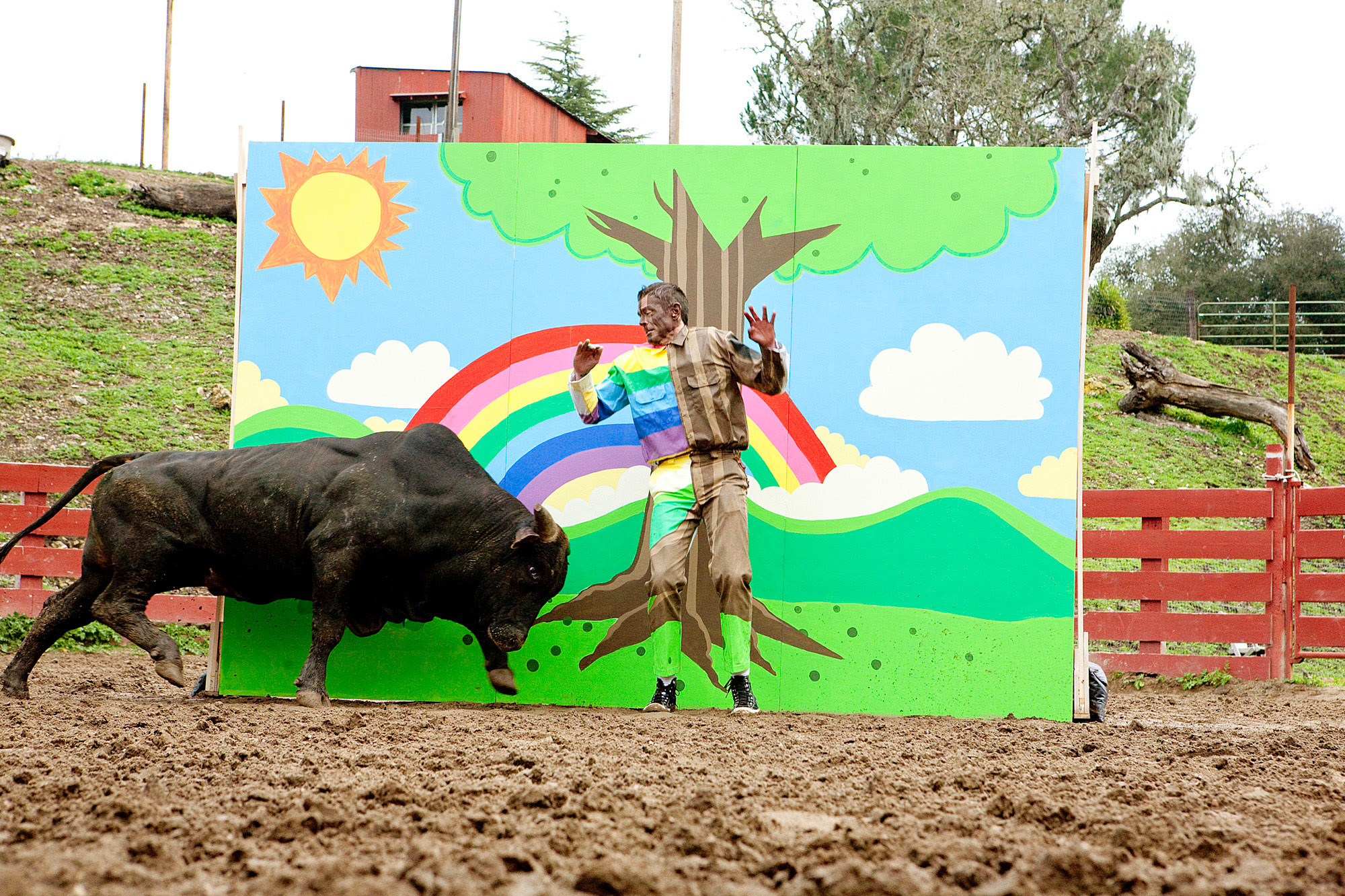 Johnny Knoxville disguised partially as a rainbow while a bull charges at him