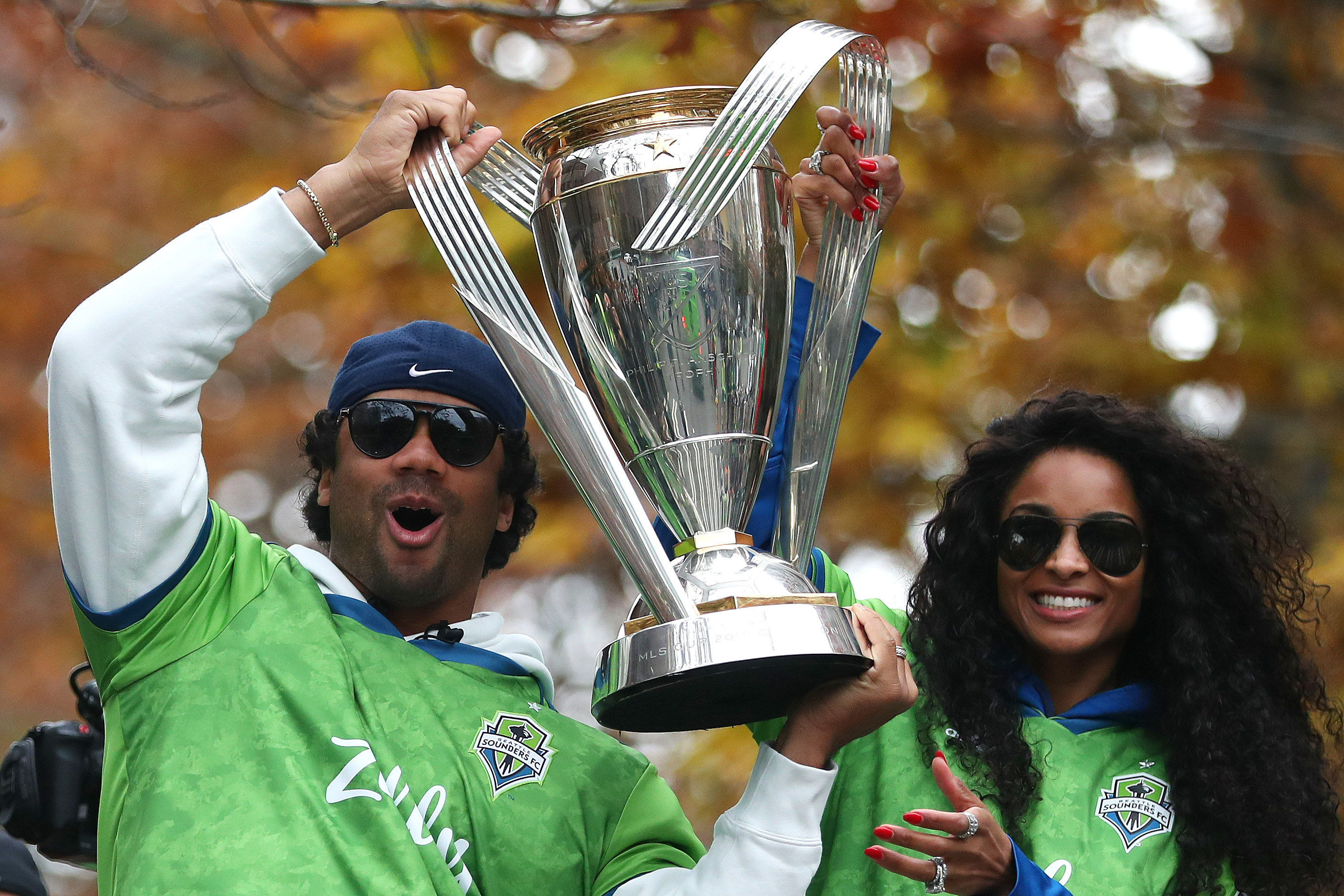 Russell holding up a trophy as Ciara smiles while standing next to him