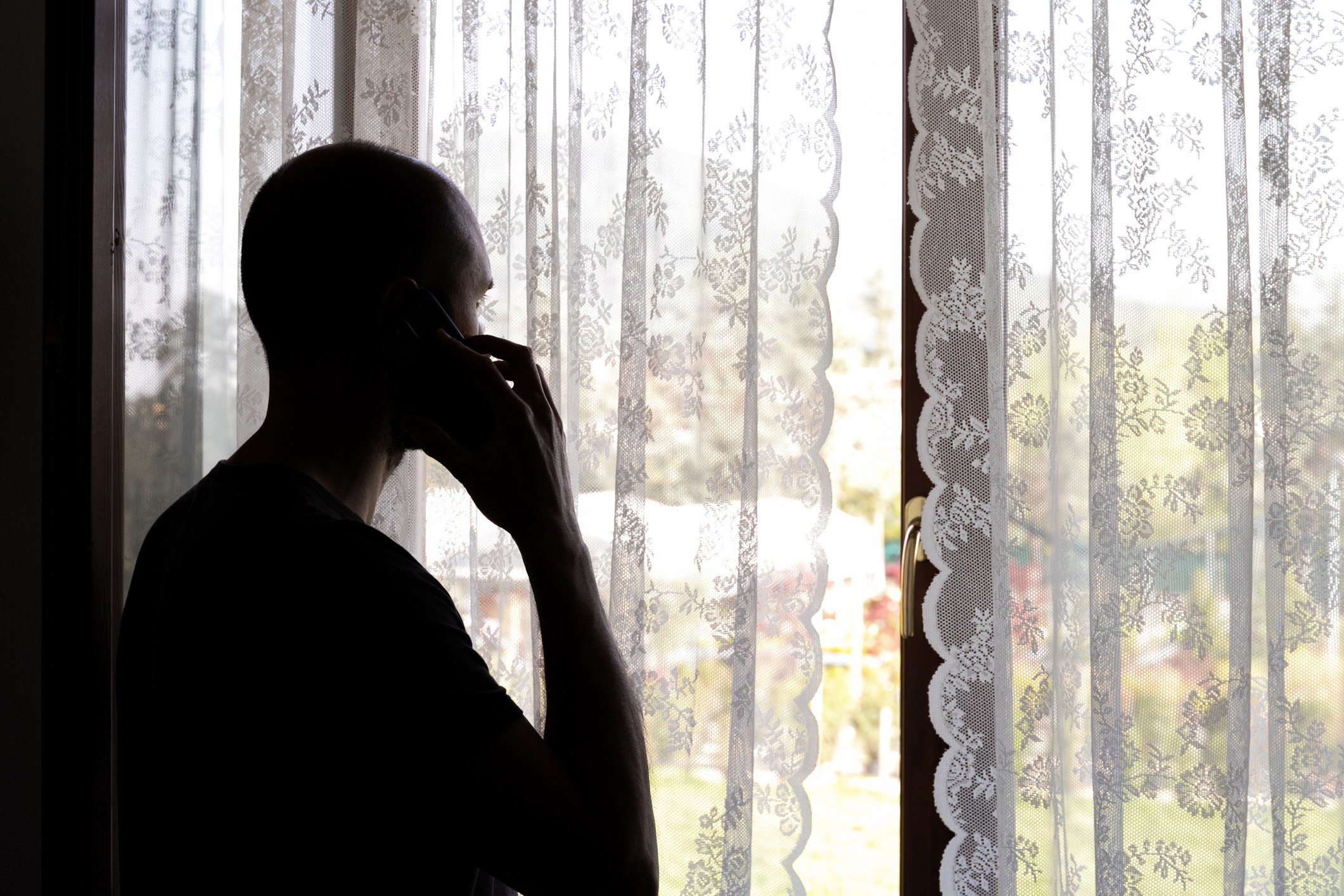 Someone alone in a room, looking out the window while talking on the phone