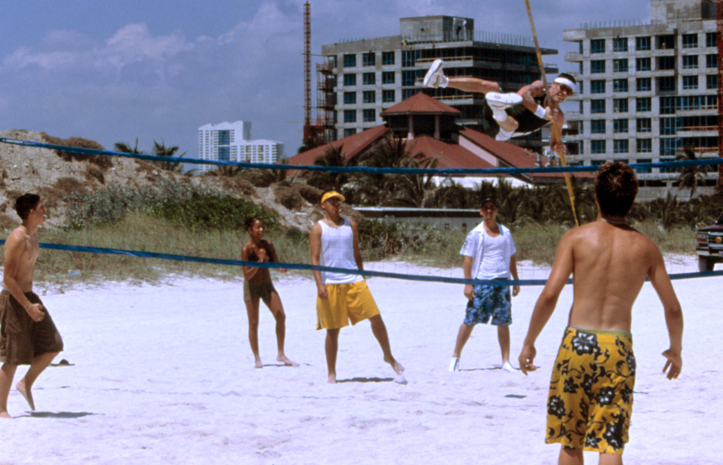 Steve-O leaping over a volleyball net using a high jump stick