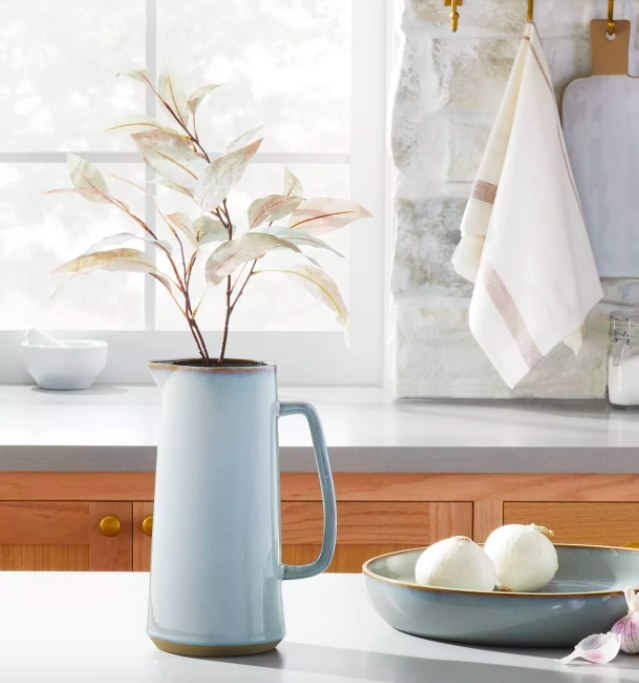 Pitcher holding flowers, sitting on a countertop with a bowl of onions next to it.