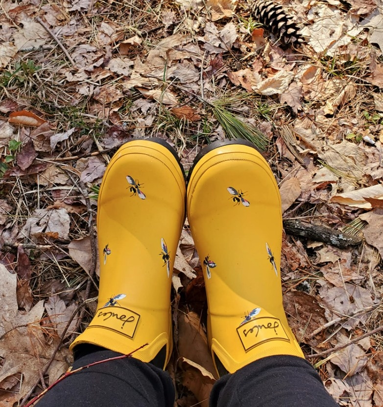 a reviewer wearing the bee patterned rain boots