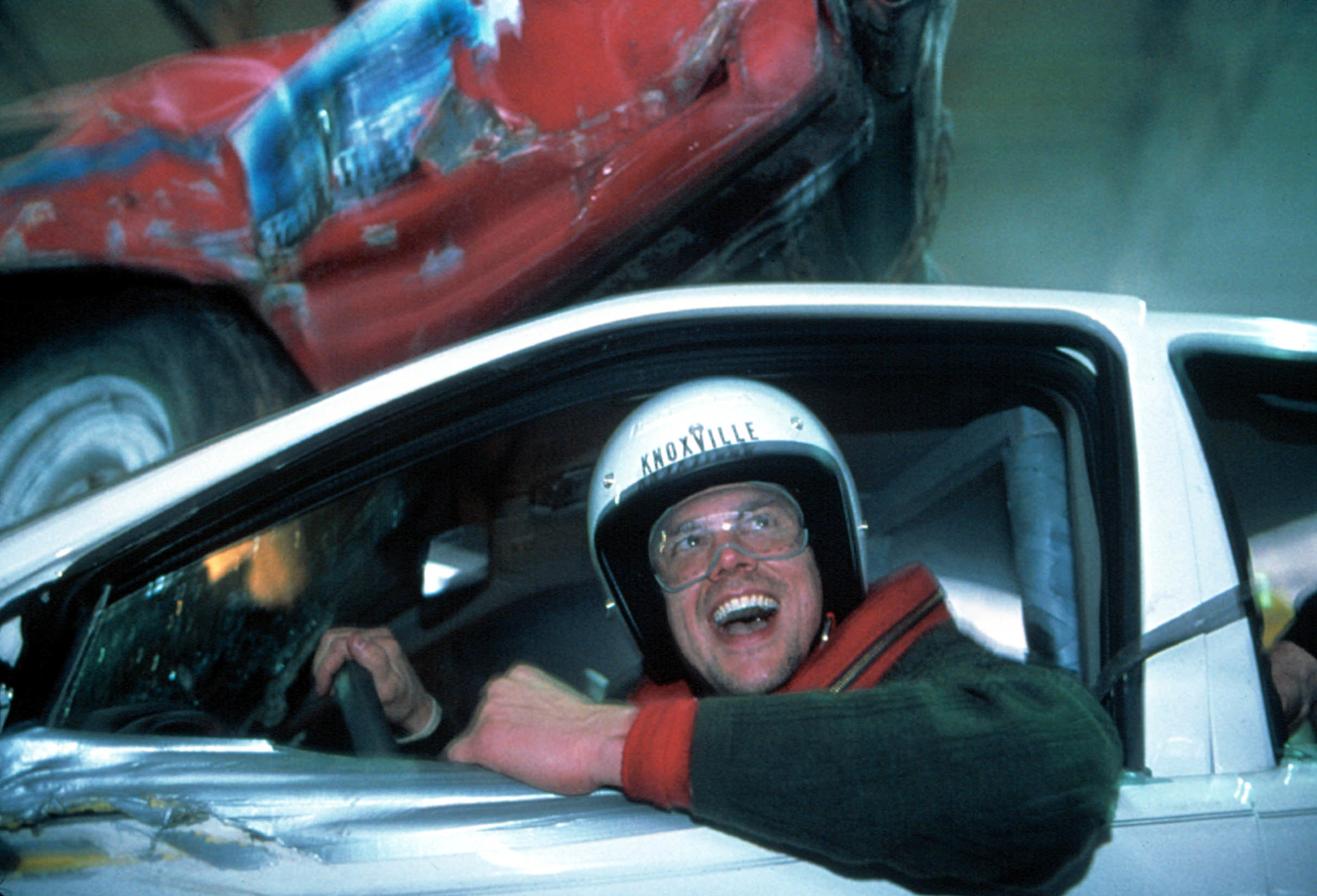 Johnny Knoxville in a car, wearing a helmet