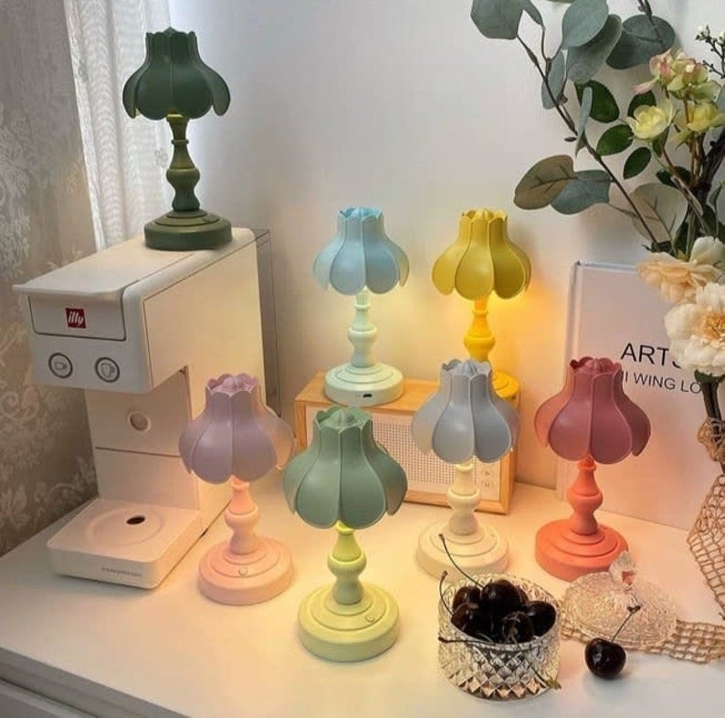 six pastel colored lamps on a white desk