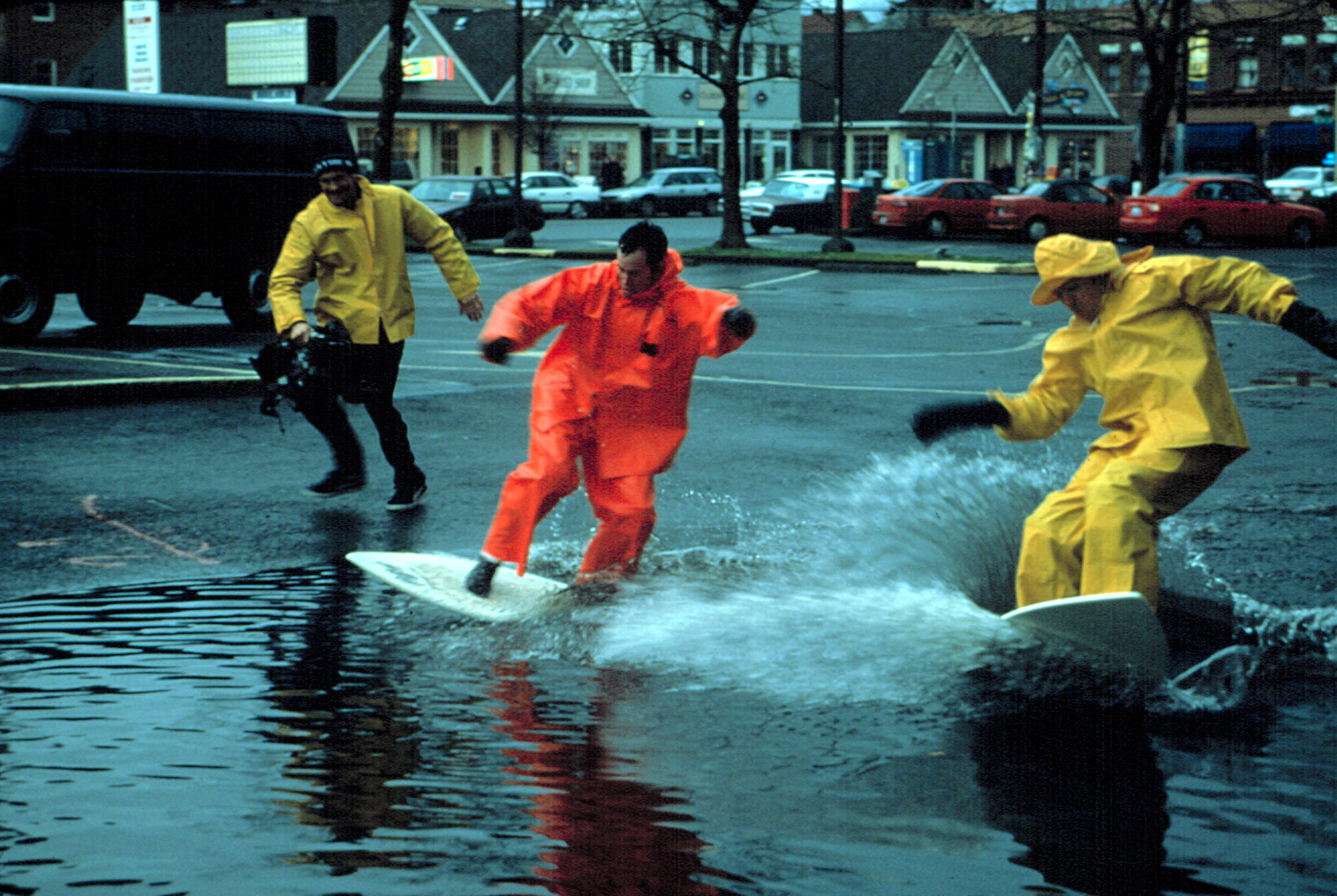 The jackass guys surfing on a flooded road