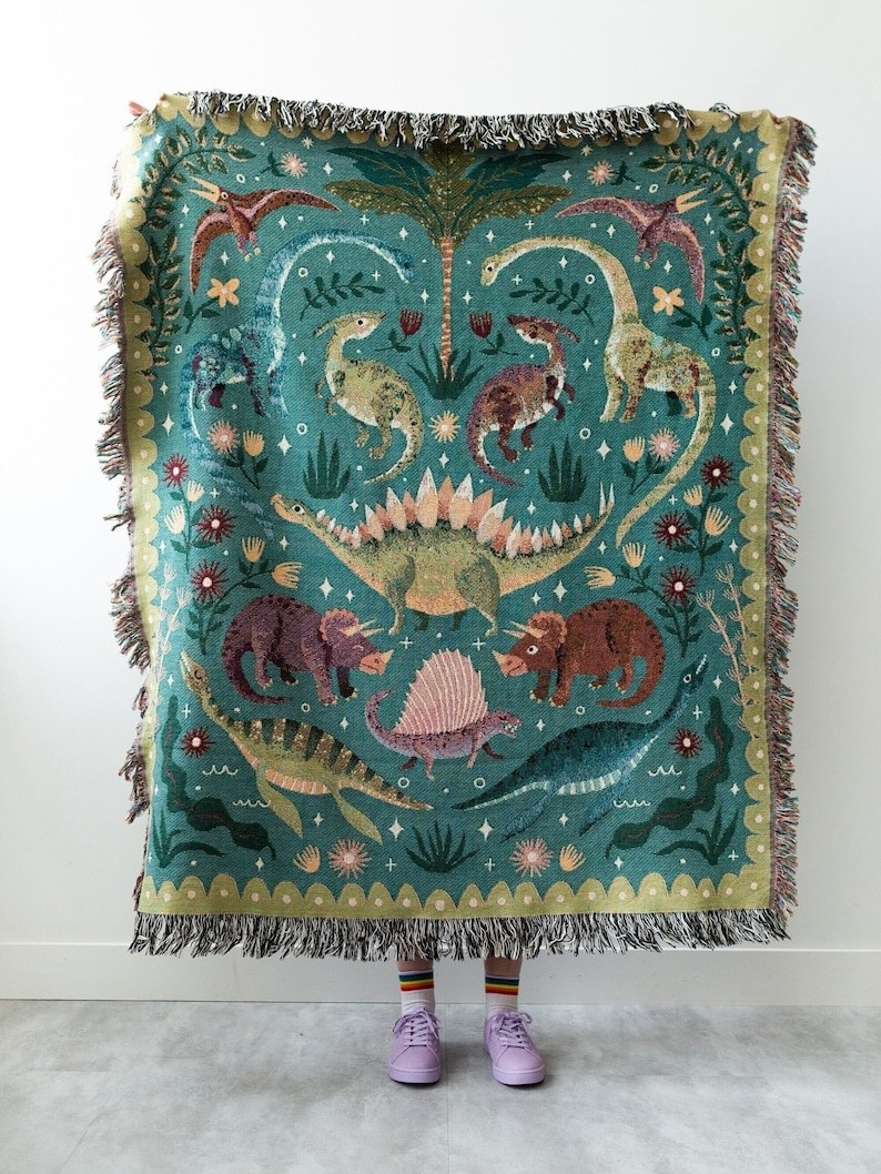 a person holding up the dino throw blanket with fringe ends