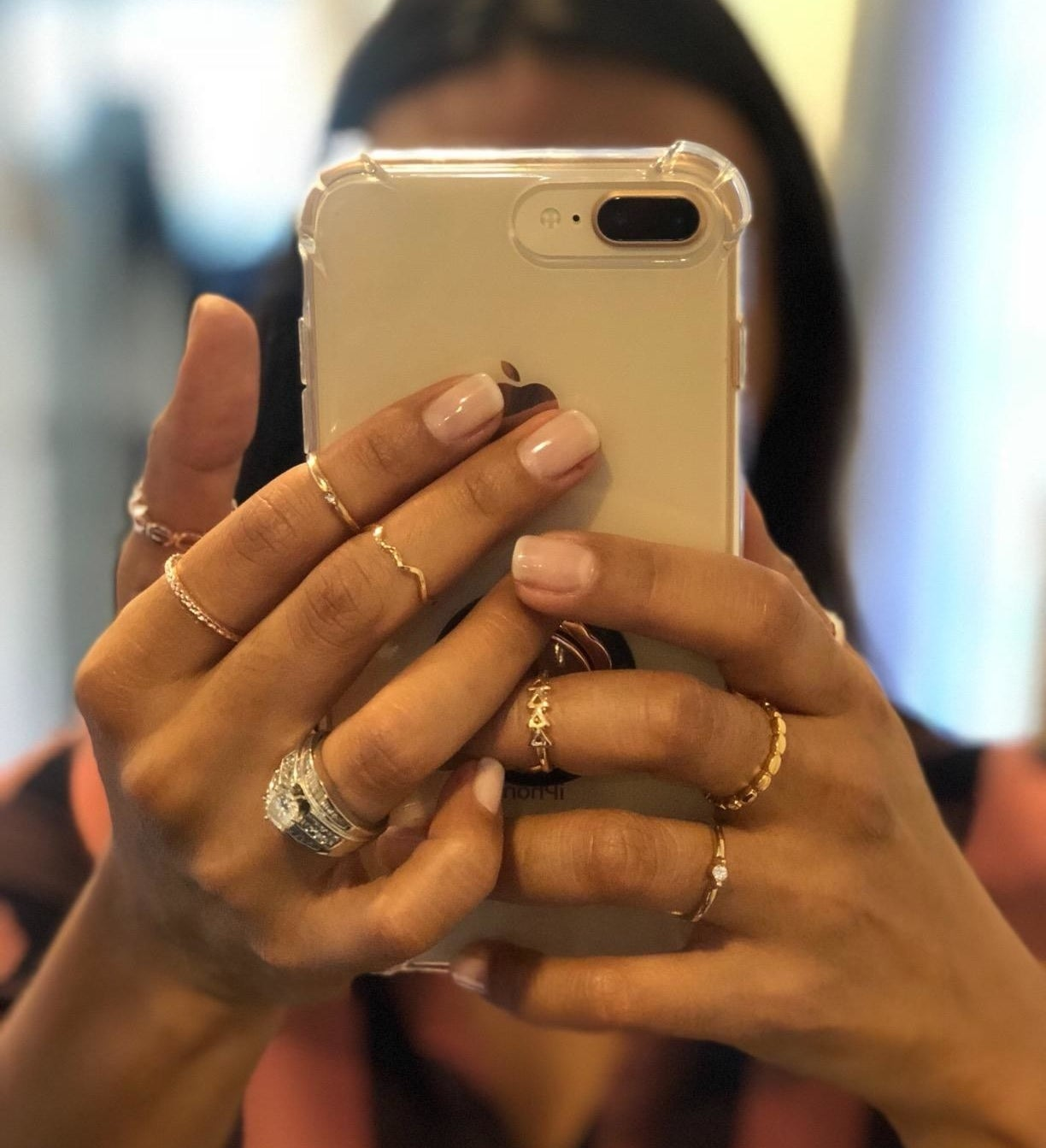 Reviewer is holding their camera up to a mirror to show off the stacked rings on their hands