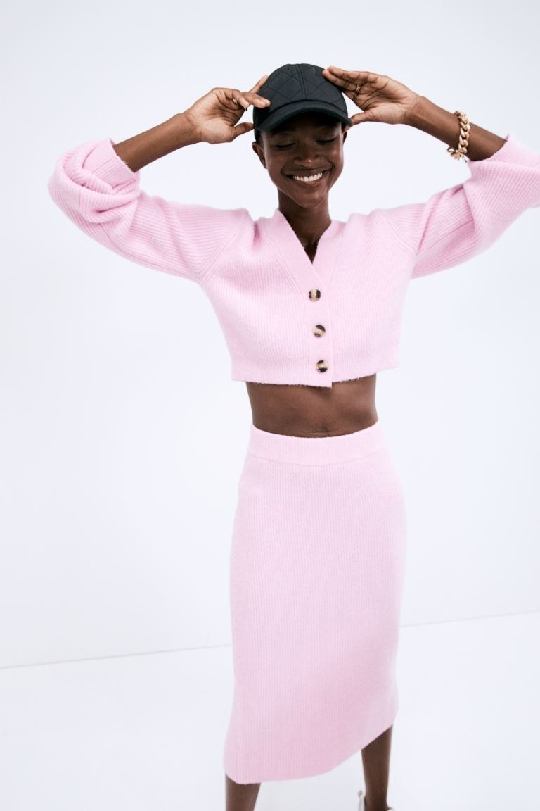 model wearing pink rib knit cardigan with matching skirt