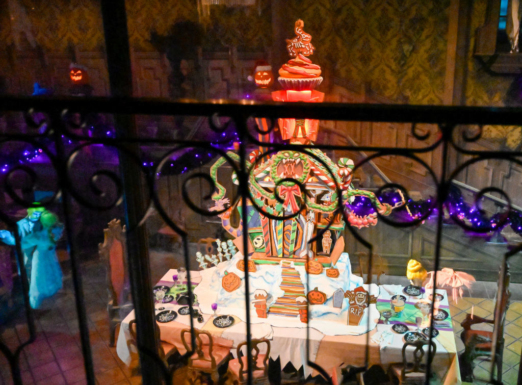 A tall gingerbread mansion with wreath, pumpkin, and ribbon decor, sits 10 feet high inside Haunted Mansion Holiday