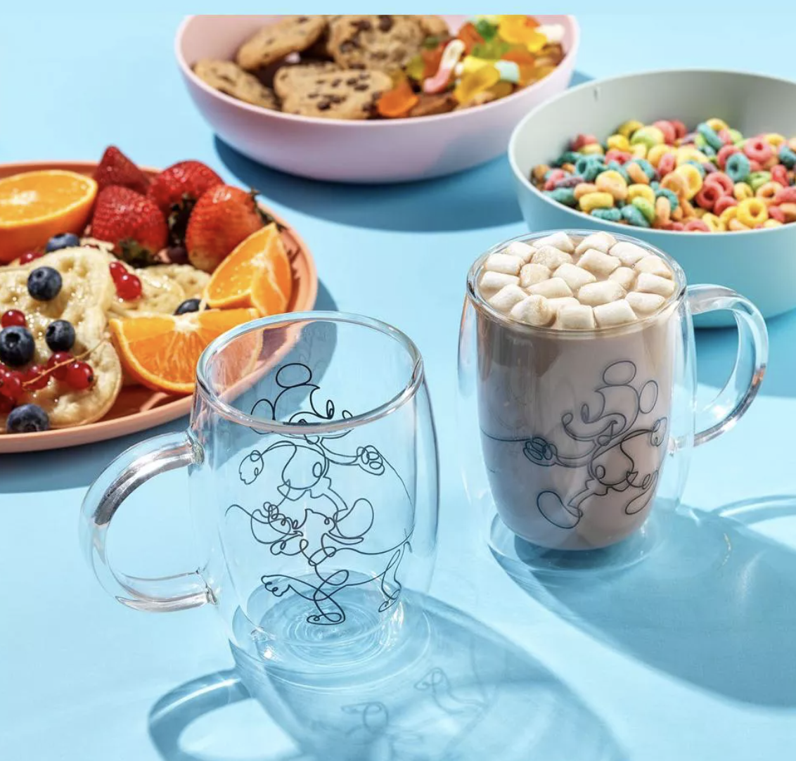 two glass mugs with an outline design of mickey and pluto on them