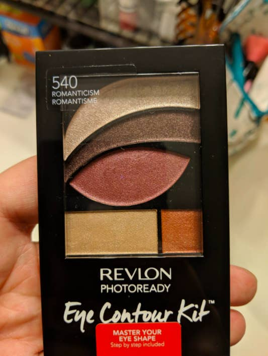 reviewer's hand holding the palette which has eyeshadow pans shaped like the area near or on the eye where the shadow should go