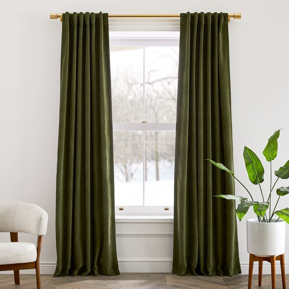 the olive velvet curtains on a gold curtain rod