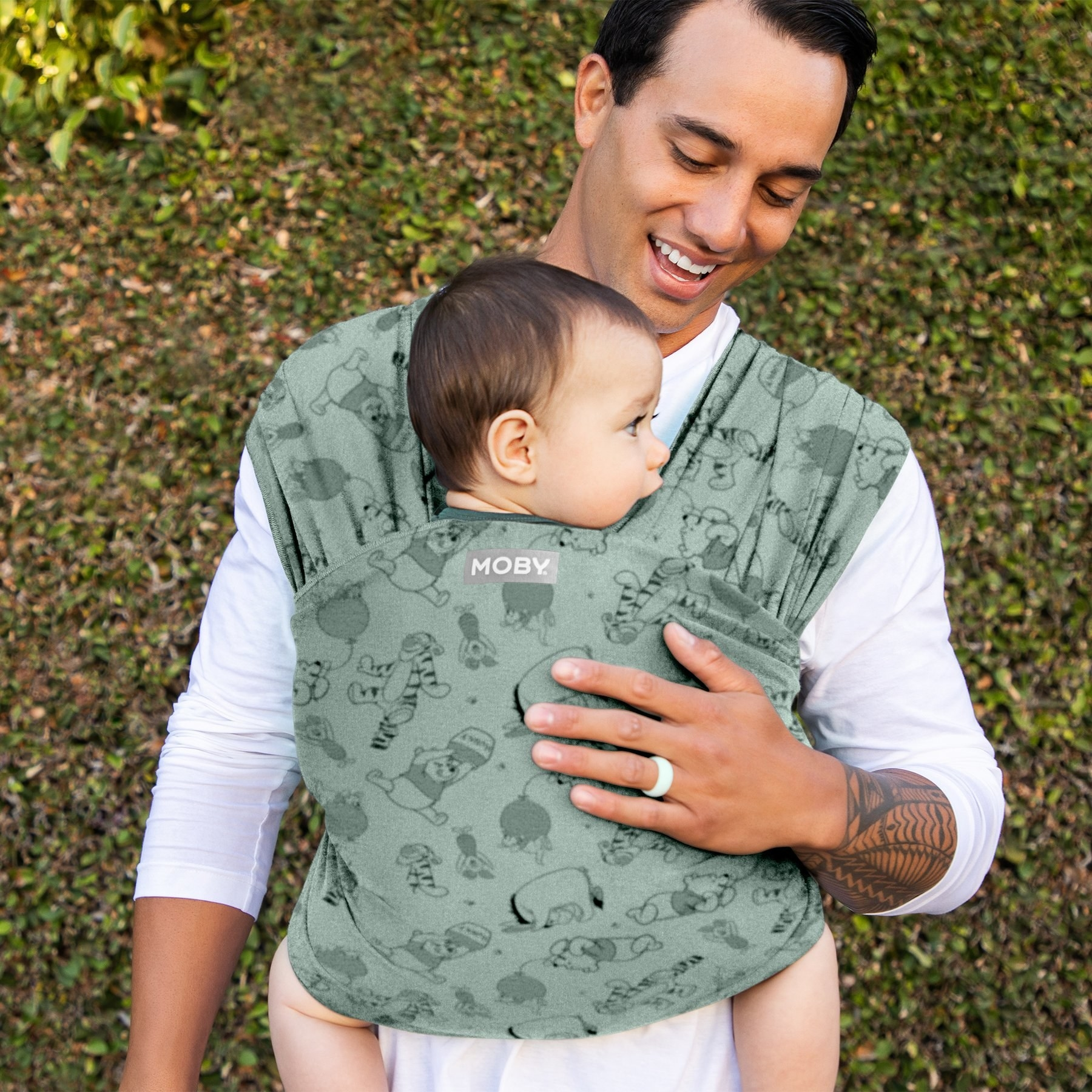 a model holding a baby in a wrap that is green with winnie the pooh characters on it