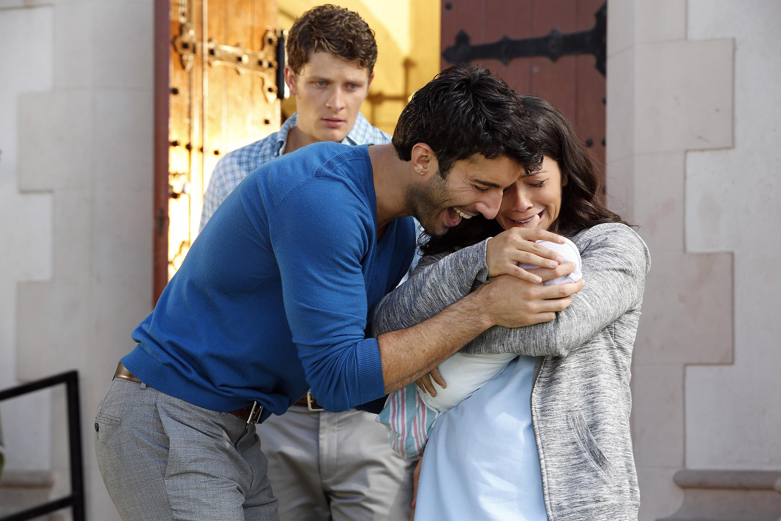 jane, michael, and rafael hugging baby