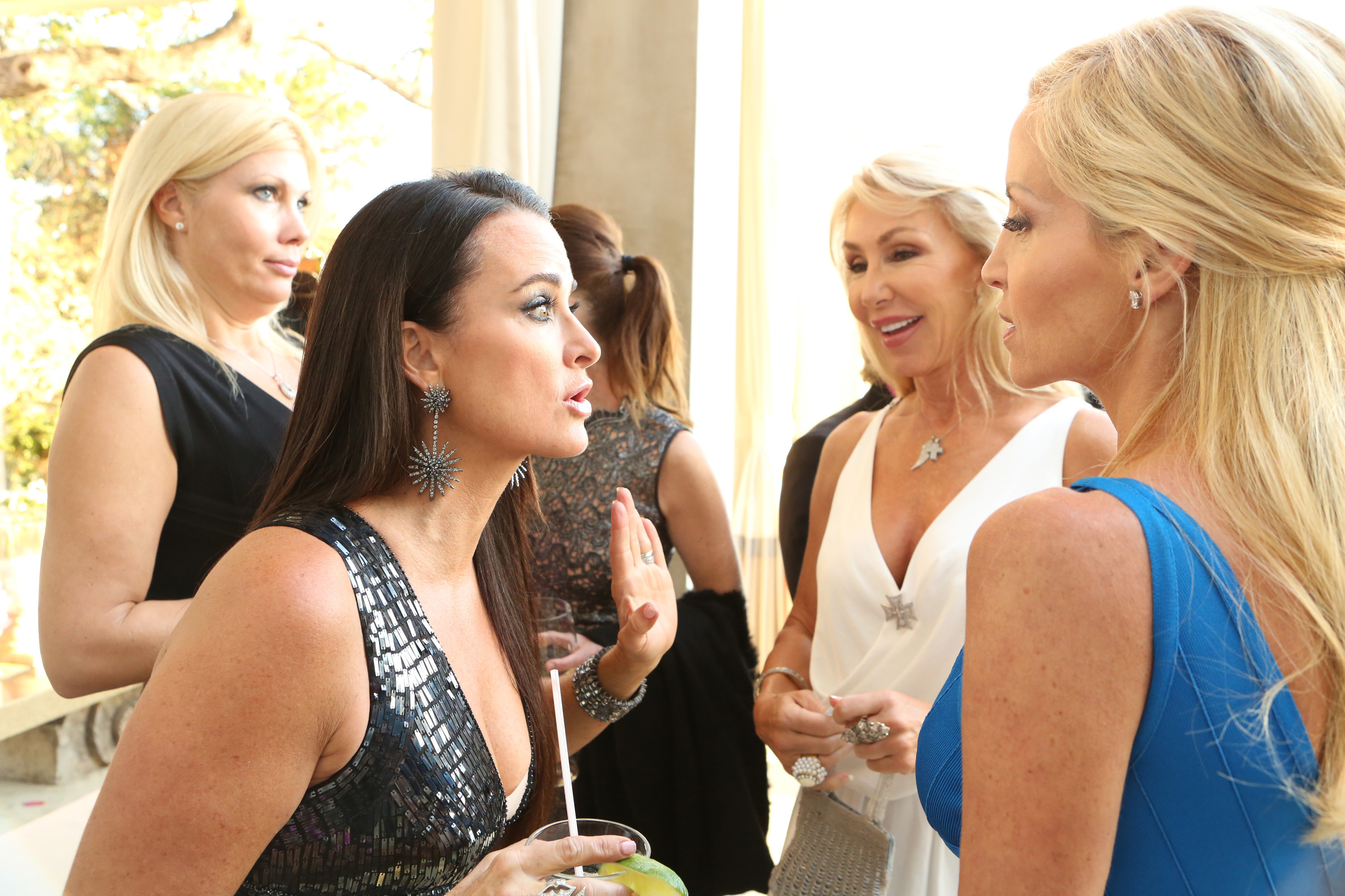 A group of the Real Housewives cast talking at a party