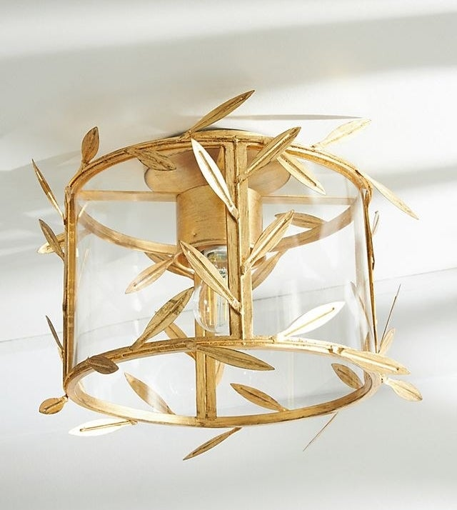 the glass and gold pendant light which is accented by metal leaves