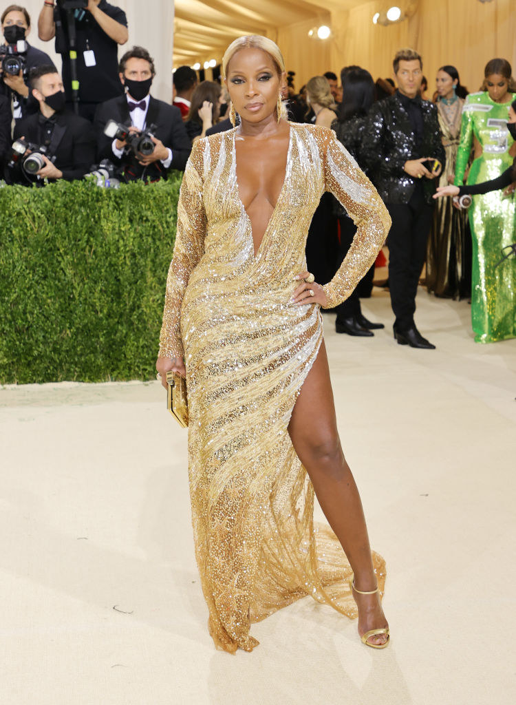 Mary J. Blige wears a long sleeve deep v-neck gown with a slit up her thigh