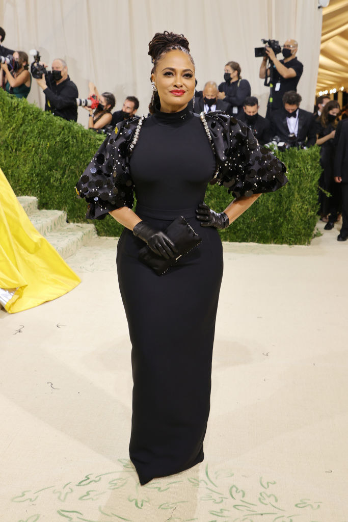 Ava DuVernay wears a dark puffy sleeve floor length gown and matching gloves