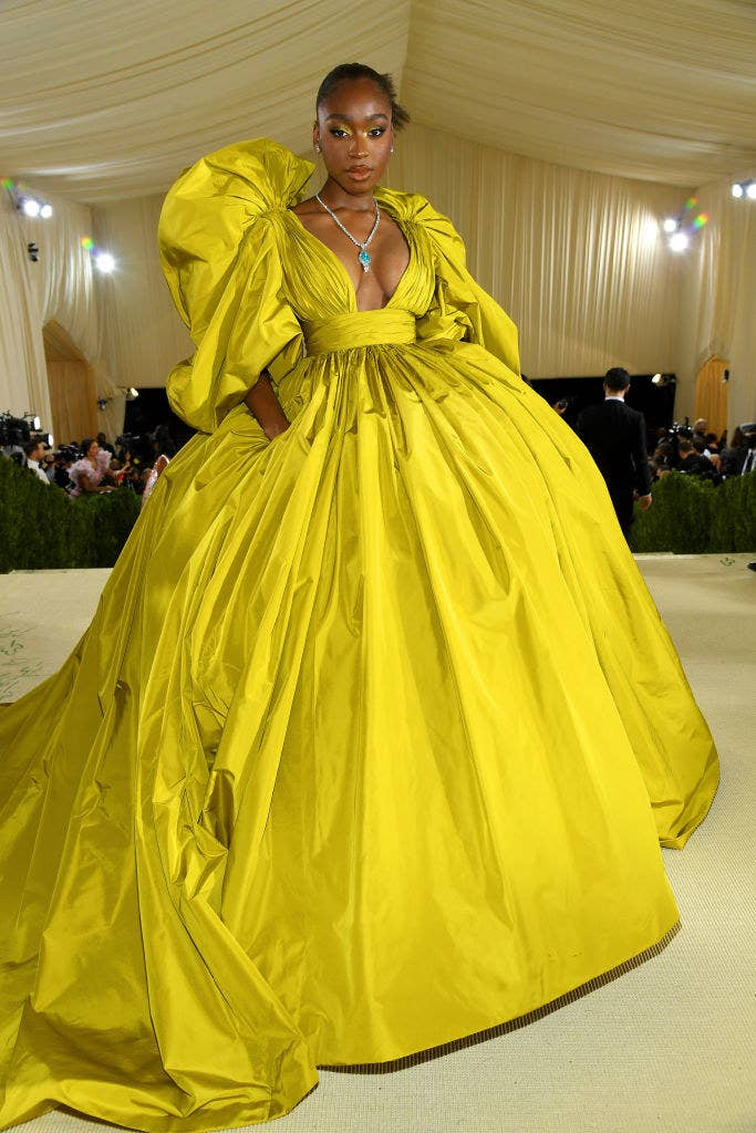 Normani wears a long sleeve brightly colored floor length gown with puffy sleeves
