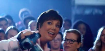Kris Jenner holding a camcorder in a scene from an Ariana Grande music video