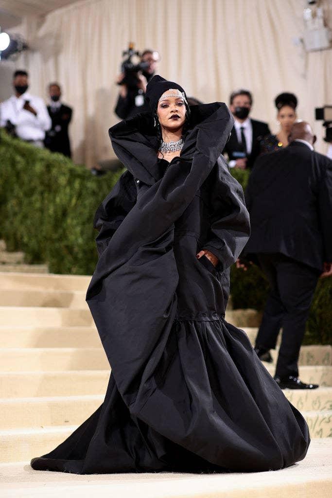 Rihanna wears a floor length dark gown with a high collar and a large diamond necklace, as well as a beanie