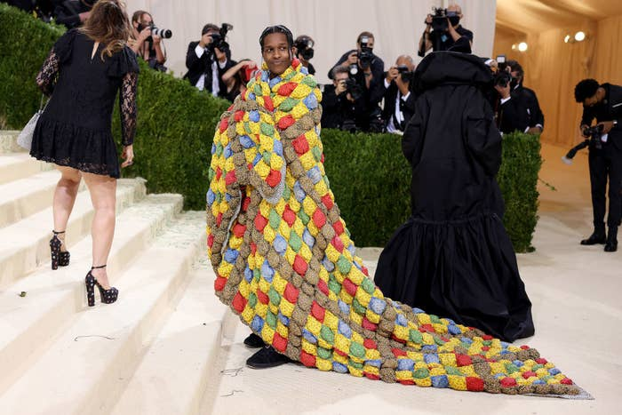A$AP Rocky stands on the Met Steps with a multicolored quilt wrapped around him