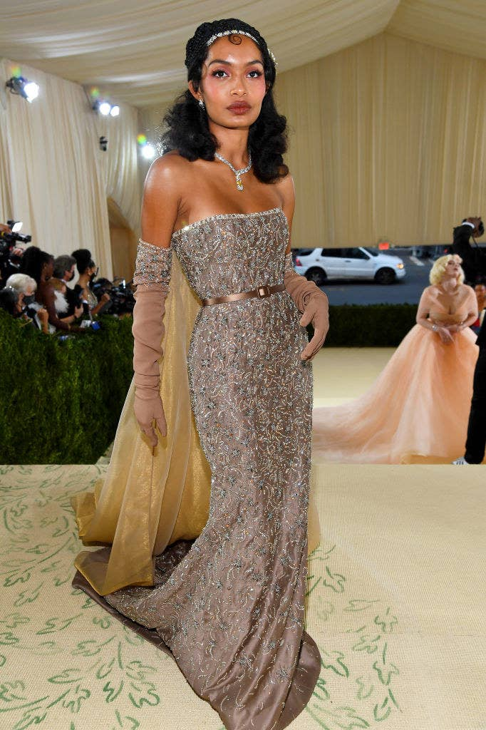 Yara Shahidi wears a floor length strapless gown with diamonds patterned sewn into it and matching elbow length gloves