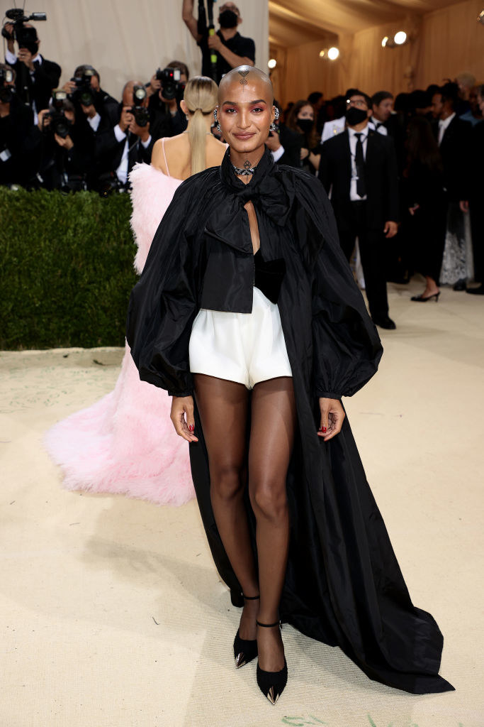 Indya Moore wears high-waisted light colored shorts and a dark long sleeve blouse with a long train