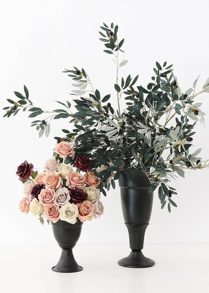 two urn-like black metal vases holding bouquets