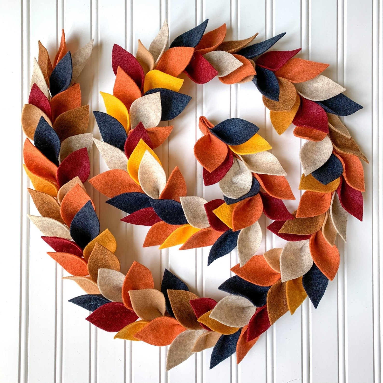 the felt garland with leaves in tan, orange, gold, blue, cream, and red