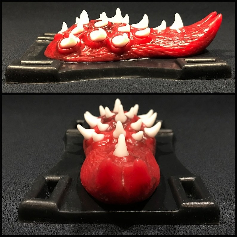 Black and red tongue-shaped grinding toy from different angles