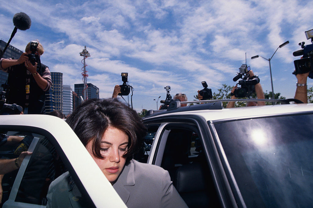 Monica Lewinsky getting into her car, surrounded by photographers