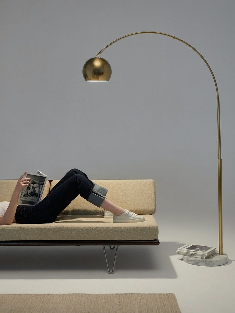 the gold floor lamp which has a marble base