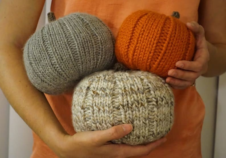 a model holding three pumpkins in various colors and sizes