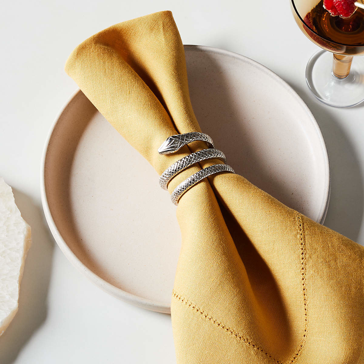 the silver snake-shaped napkin ring on a gold napkin