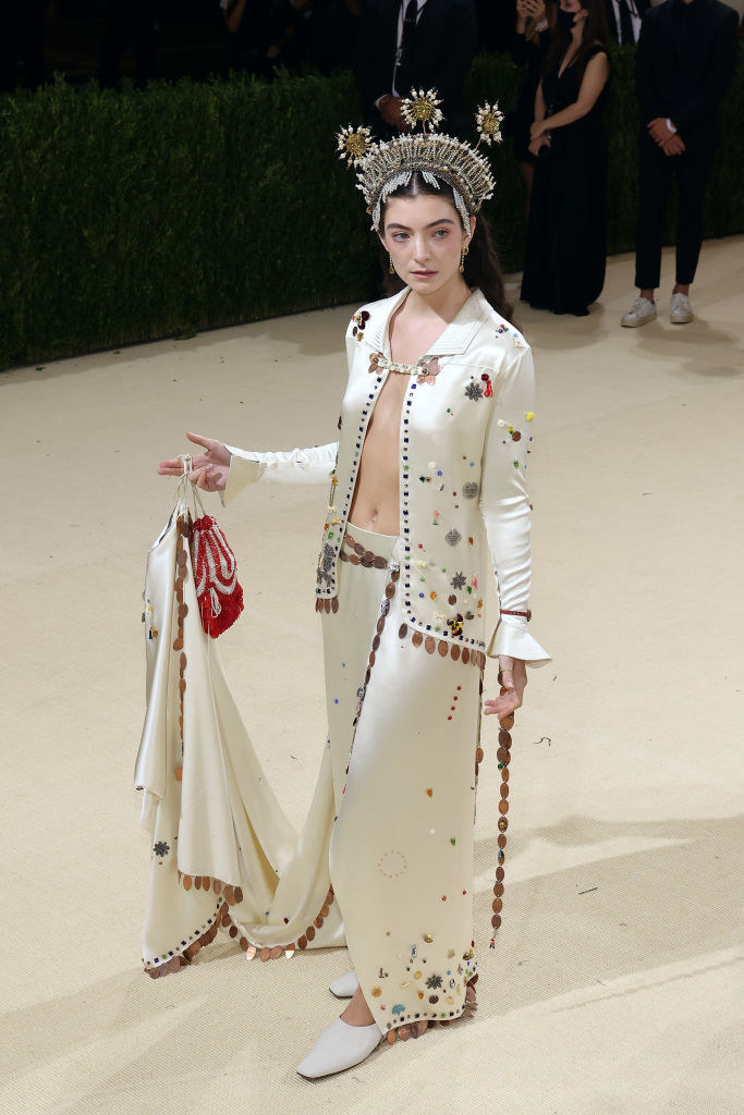 Lorde wore an open jacket with a matching satin skirt and headpiece