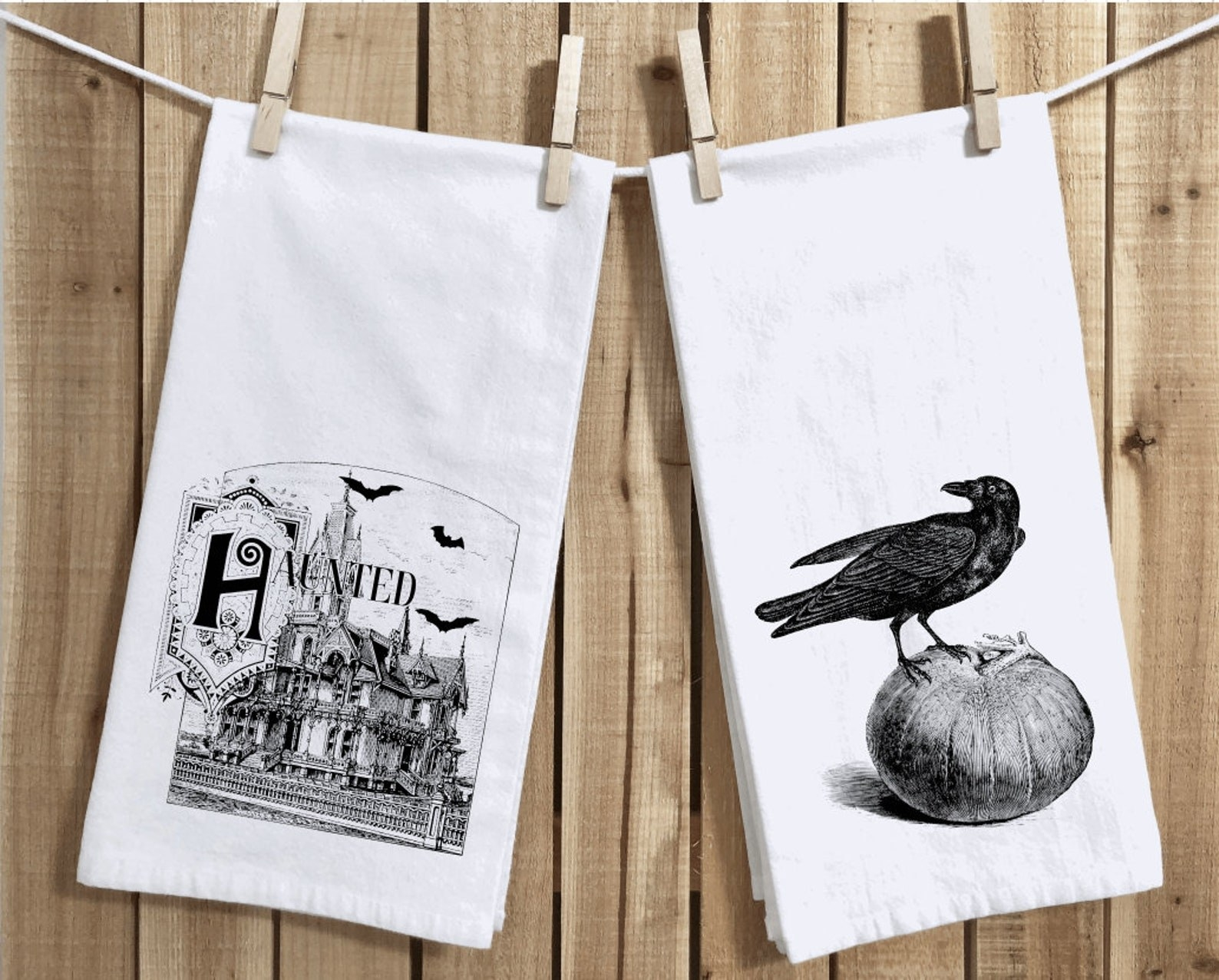 two white tea towels; one with a haunted house design and one with a crow standing on a pumpkin