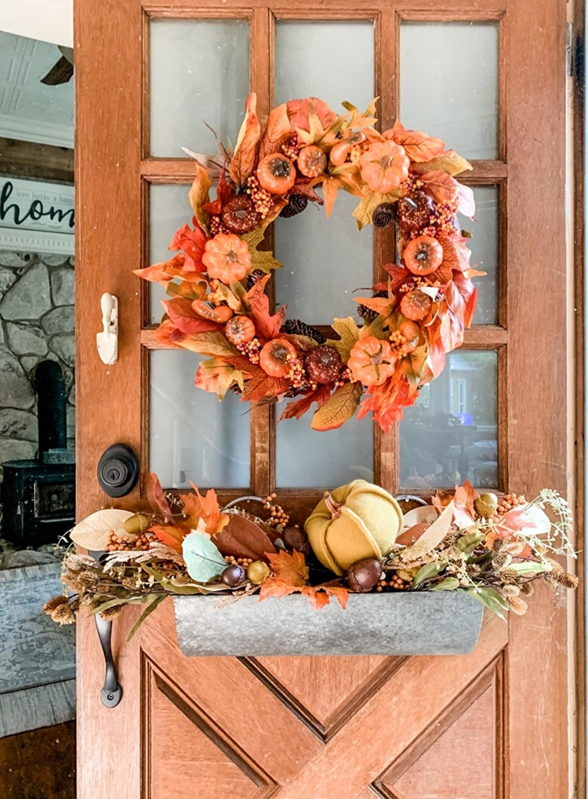 The wreath full of colorful artificial leaves and berries and mini pumpkins on a reviewer's door